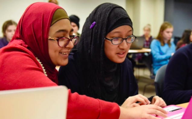 Two girls wearing hijabs smile together at a laptop screen