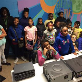 Girls at a techshop in Chicago smile for a group photo