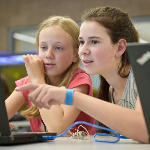 Two girls point to a laptop screen during a Colorado TechCamp
