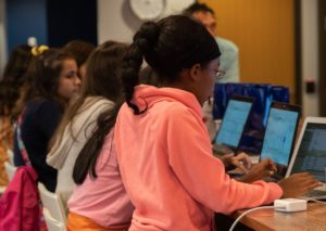 Girls look intently at their laptops during a workshop