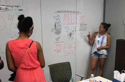 After using the whiteboard walls, a girl shows off her web concepts work