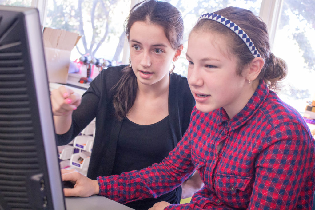 Two teen girls share a computer and work together