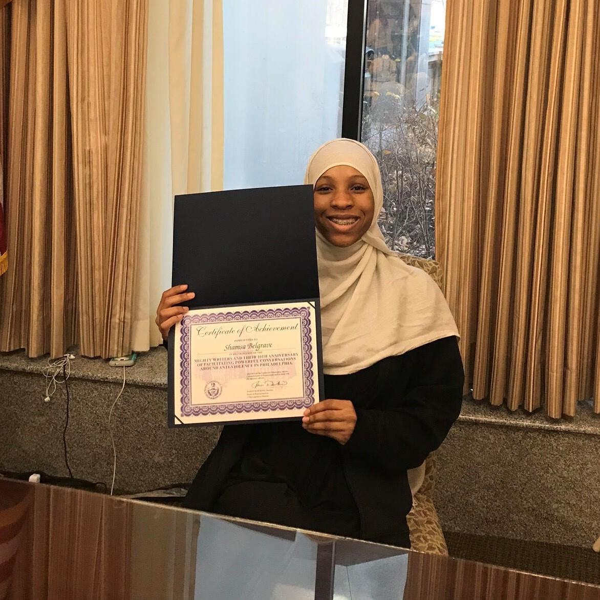 Shamsa smiling and holding up an award