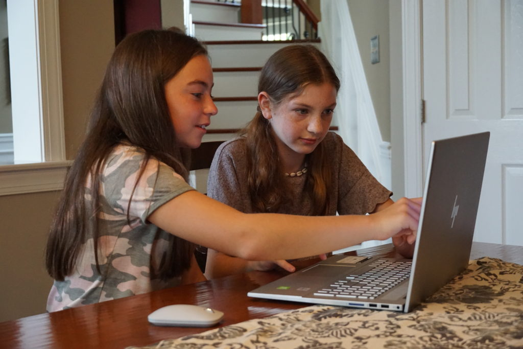 Two girls work together at a computer on their kitchen table